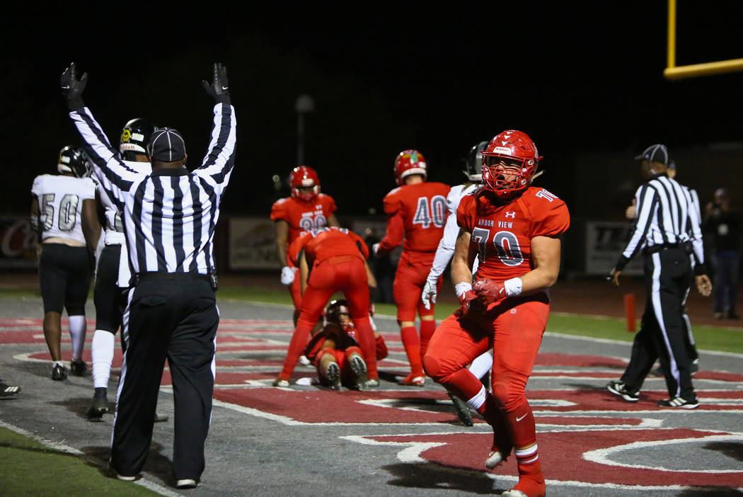 Arbor View's Tyler Kincheloe (70) celebrates after Arbor View's Logan Bollinger (10) scores the winning touchdown over Desert Pines during second half of the Mountain Region football semifinal gam ...