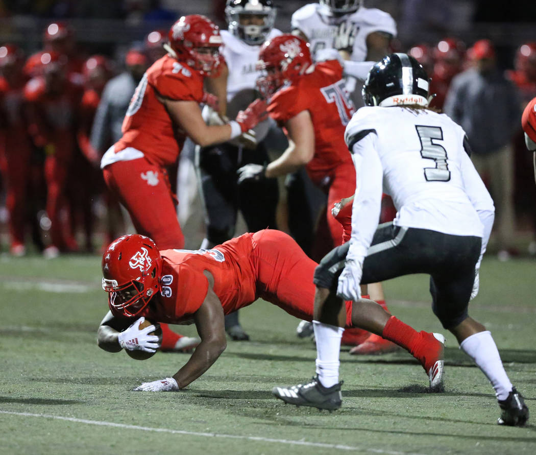 Arbor View's Darius Williams (30) goes down with the ball while under pressure from Desert Pines' Darius Stewart (5) during second half of the Mountain Region football semifinal game at Arbor View ...
