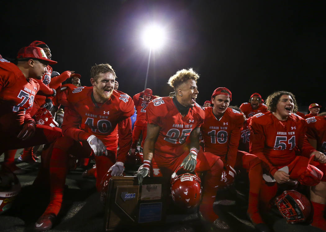 Arbor View's Kyle Graham (25) holds the trophy as the team celebrates their win over Faith Lutheran in the Class 4A Mountain Region championship game at Arbor View High School in Las Vegas on Frid ...