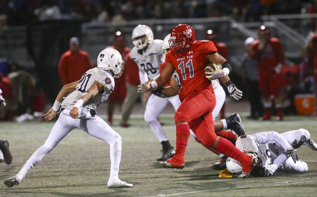 Arbor View's J.J. Tuinei (11) runs the ball after an interception against Faith Lutheran during the first half of the Class 4A Mountain Region championship game at Arbor View High School in Las Ve ...