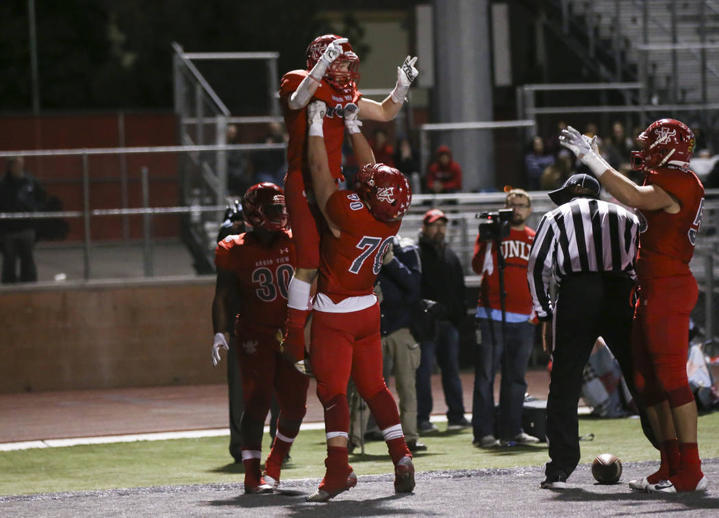 Arbor View's Tyler Kincheloe (70) celebrates a touchdown by Arbor View's Justin Hausner (13) during the second half of the Class 4A Mountain Region championship game at Arbor View High School in L ...