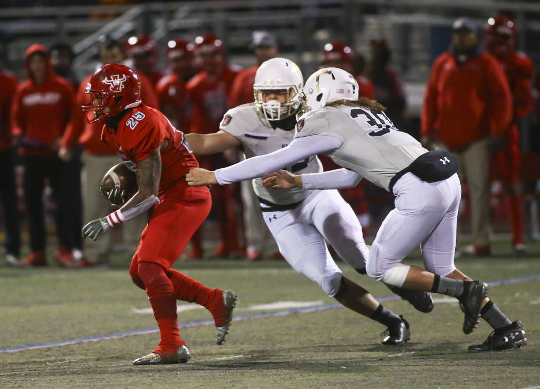 Arbor View's Kyle Graham (25) runs the ball past Faith Lutheran's Keisel Perez, left, and Sean Nolan (30) during the first half of the Class 4A Mountain Region championship game at Arbor View Hig ...