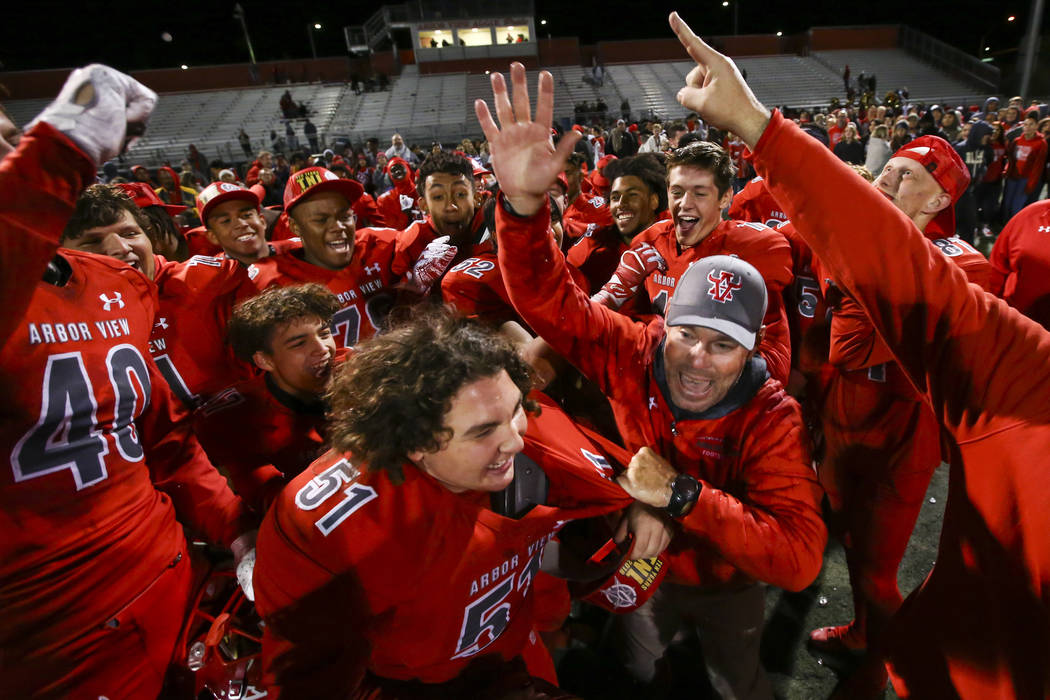 Arbor View head coach Dan Barnson, right, joins his players in celebrating their win over Faith Lutheran in the Class 4A Mountain Region championship game at Arbor View High School in Las Vegas on ...