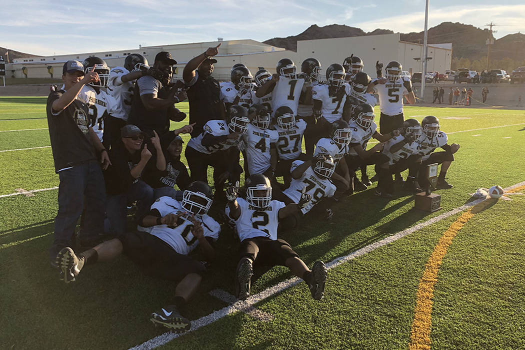 Spring Mountain football players pose with the Class 1A state championship trophy after a 60-38 victory over Tonopah at Beatty High School on Saturday, Nov. 17, 2018. (Sam Gordon/Las Vegas Review- ...