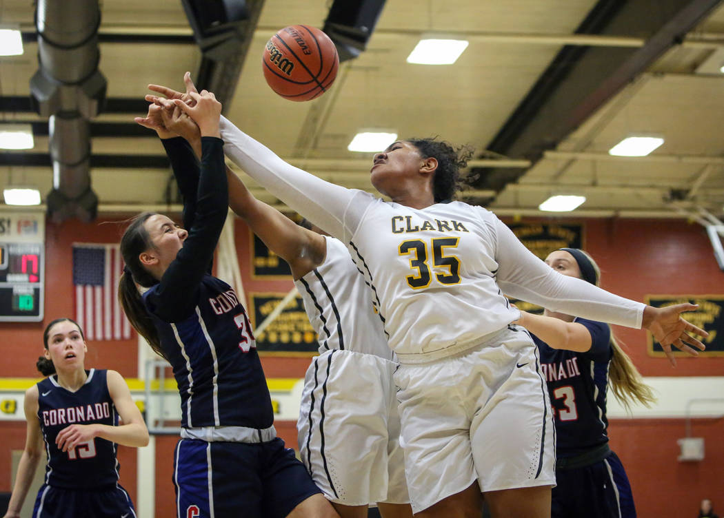 Coronado's Alexee Johnson (35) and Clark's Coraly Dupree (35) reach to grab the ball during a basketball game at Clark High School in Las Vegas, Monday, Nov. 26, 2018. Caroline Brehman/Las Vegas R ...