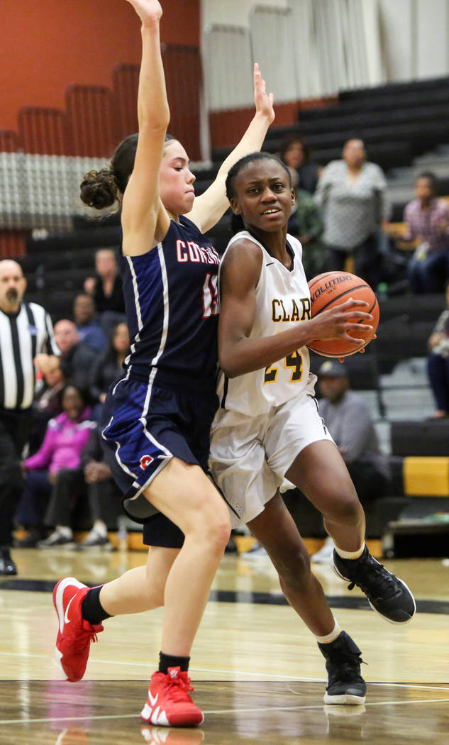 Clark's Al'ynnay Godfrey (24) runs with the ball while under pressure from Coronado's Gabbie Etopio (15) during a basketball game at Clark High School in Las Vegas, Monday, Nov. 26, 2018. Caroline ...