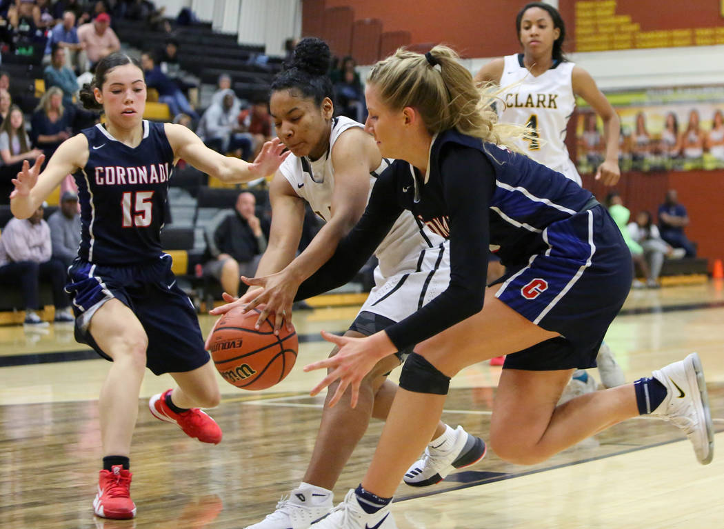 Clark's Marieka Dent (3) reaches for the ball while under pressure from Coronado's Gabbie Etopio (15) and Haley Morton (45) during a basketball game at Clark High School in Las Vegas, Monday, Nov. ...