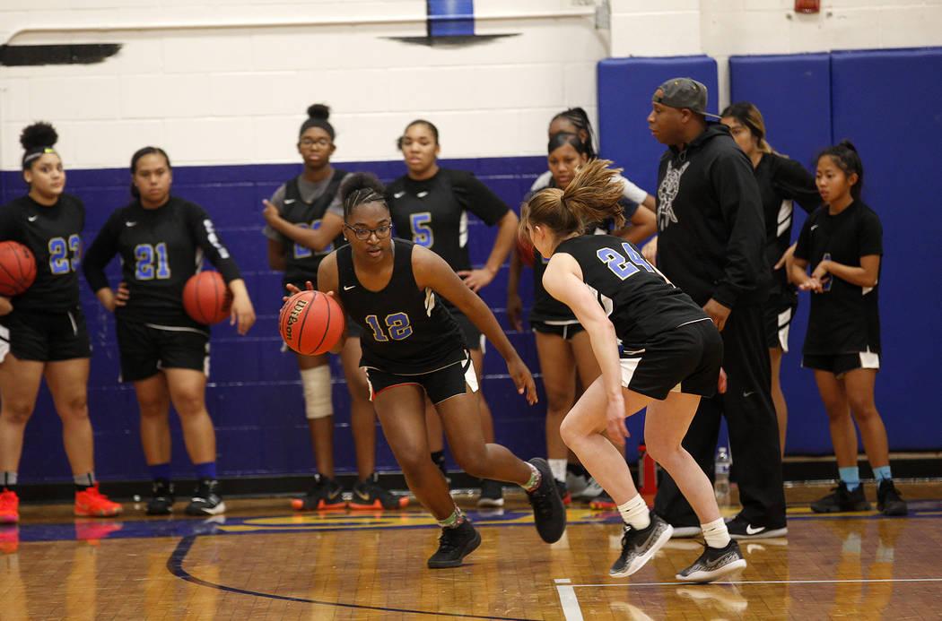 Shania Harper (12), a senior forward on the Sierra Vista High School varsity basketball team, practices drills with teammate Ashley Hansen (24) at Sierra Vista High School in Las Vegas, Monday, No ...