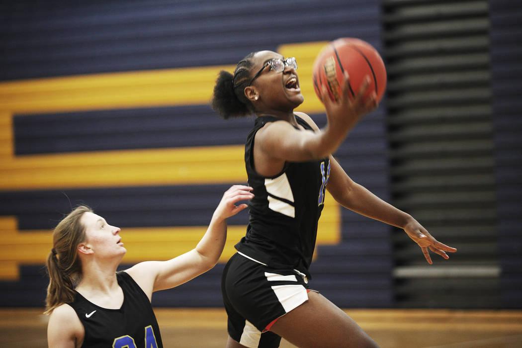 Shania Harper (12), a senior forward on the Sierra Vista High School varsity basketball team, shoots past teammate Ashley Hansen (24) during practice at Sierra Vista High School in Las Vegas, Mond ...