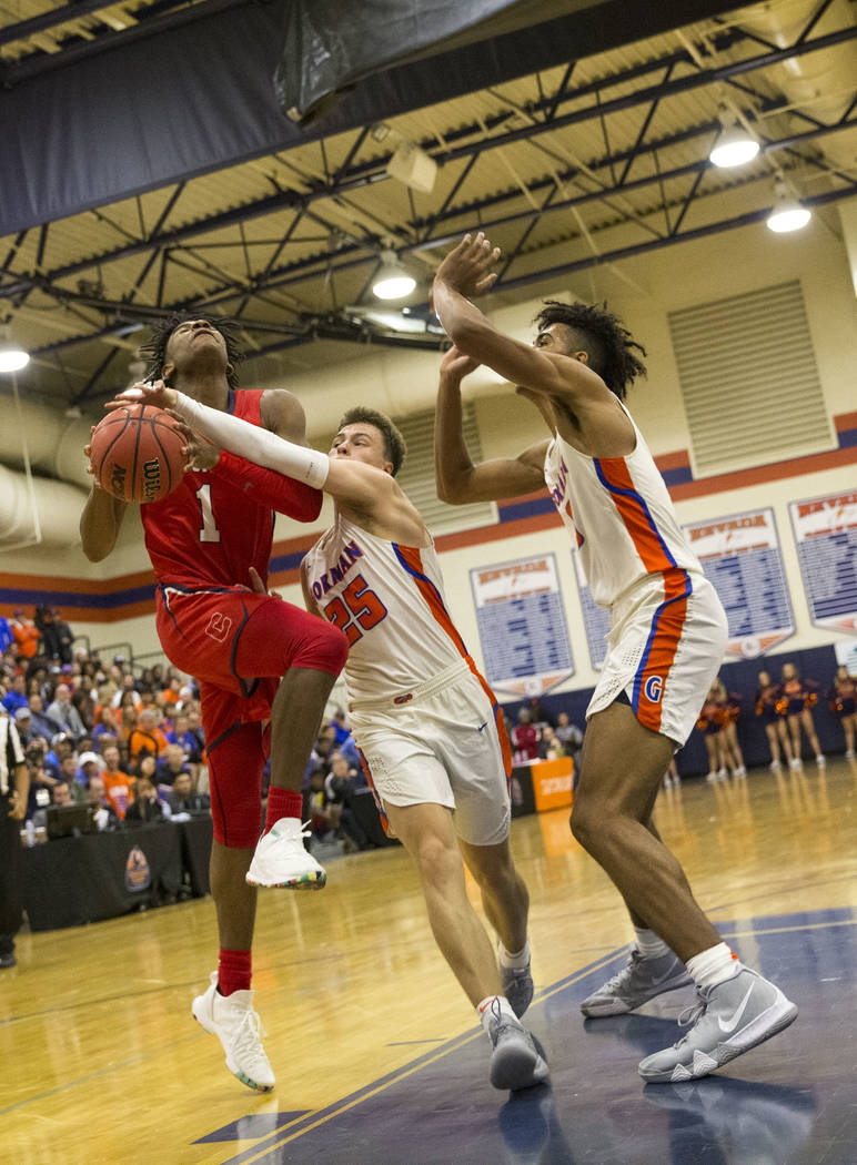 Coronado's Jaden Hardy (1) gets blocked by Bishop Gorman's Chance Michels (25) during the second half of a varsity basketball game at Bishop Gorman High School in Las Vegas on Thursday, Nov. 29, 2 ...