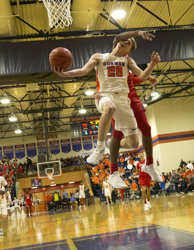 Bishop Gorman's Noah Taitz (20) gets fouled by a Coronado defender during the second half of a varsity basketball game at Bishop Gorman High School in Las Vegas on Thursday, Nov. 29, 2018. Richard ...