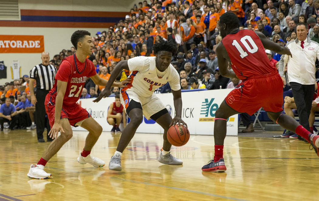 Bishop Gorman's Will McClendon (1) looks for an opening through Coronado's Max Howard (21) and Tyrell Hunt (10) during the first half of a varsity basketball game at Bishop Gorman High School in L ...