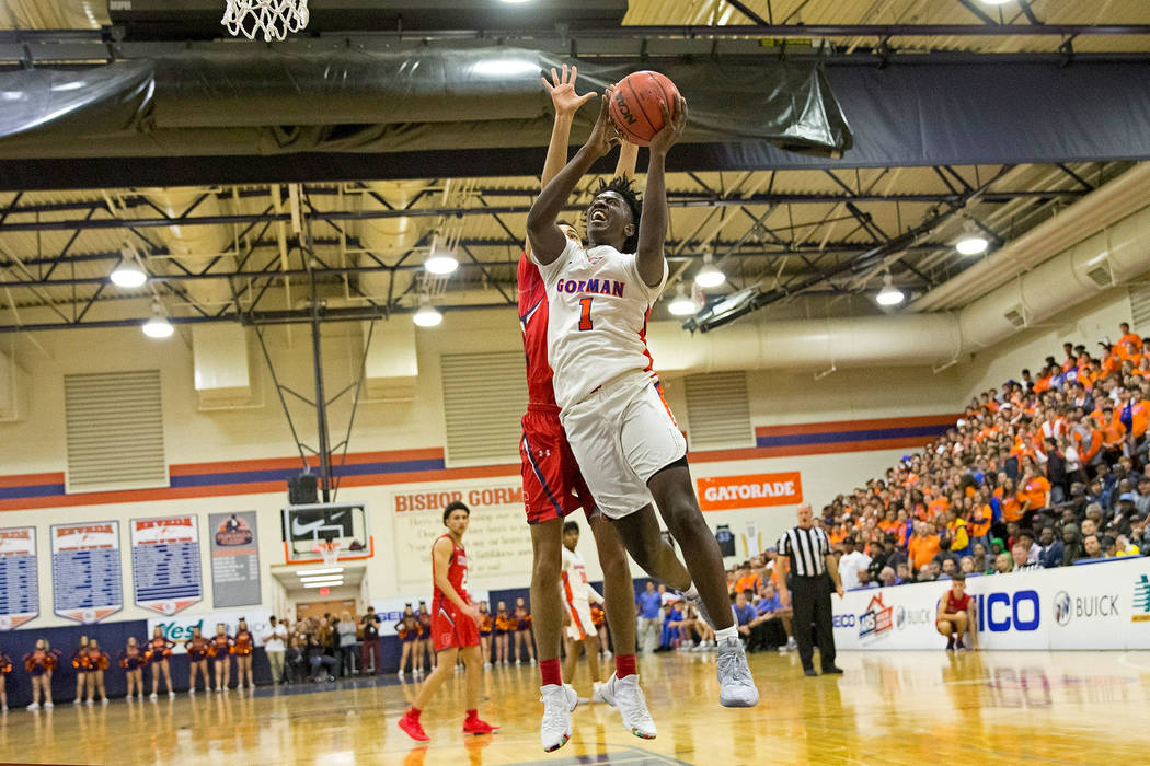 Bishop Gorman's Will McClendon (1) goes up for a shot in front of Coronado's Max Howard (21) during the first half of a varsity basketball game at Bishop Gorman High School in Las Vegas on Th ...
