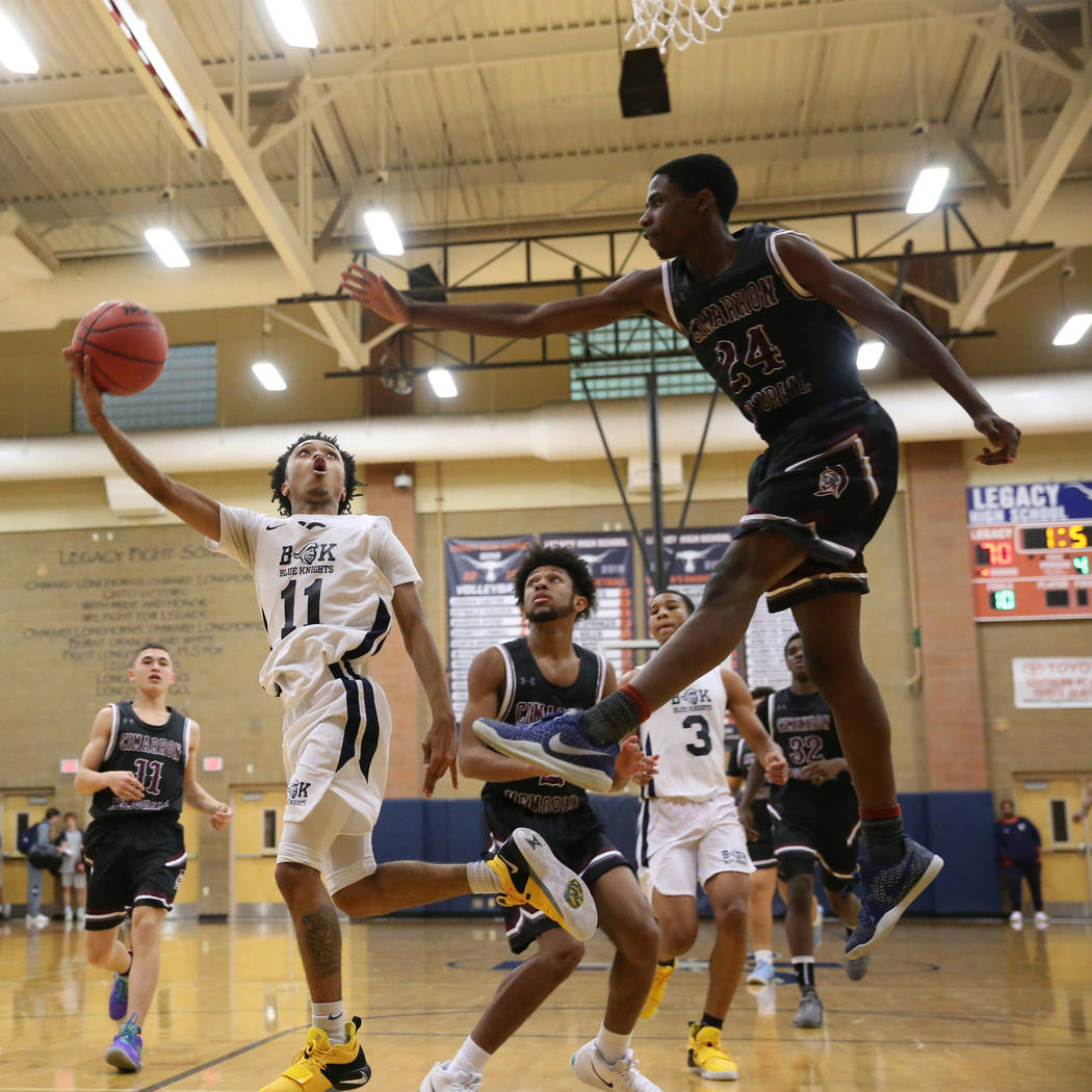 Democracy Prep's Justous Harvey (11) goes up for a shot against Cimarron-Memorial's Malik Kennedy (24) in their basketball game at Legacy High School in North Las Vegas, Friday, Nov. 30, 2018. Eri ...