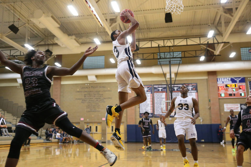 Democracy Prep's Chancelor Johnson (3) goes up for a shot against Cimarron-Memorial's JaiTwan Golden (23) in their basketball game at Legacy High School in North Las Vegas, Friday, Nov. 30, 2018. ...