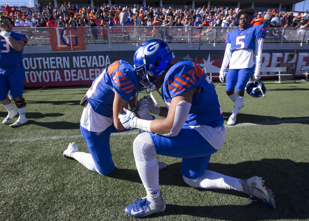 Bishop Gorman's Lincoln Tuioti-mariner (20), left, and Ishe Smith Jr (30) pray before playing Reno's Bishop Manogue in the NIAA high school football championship at Sam Boyd Stadium in Las Vegas o ...
