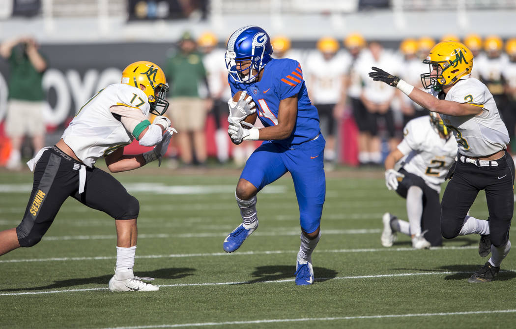 Bishop Gorman wide receiver Rome Odunze (4) runs the ball through Bishop Manogue's Preston Helu (17) and Mateo Reviglio (3) during the second half of the NIAA high school football championship at ...
