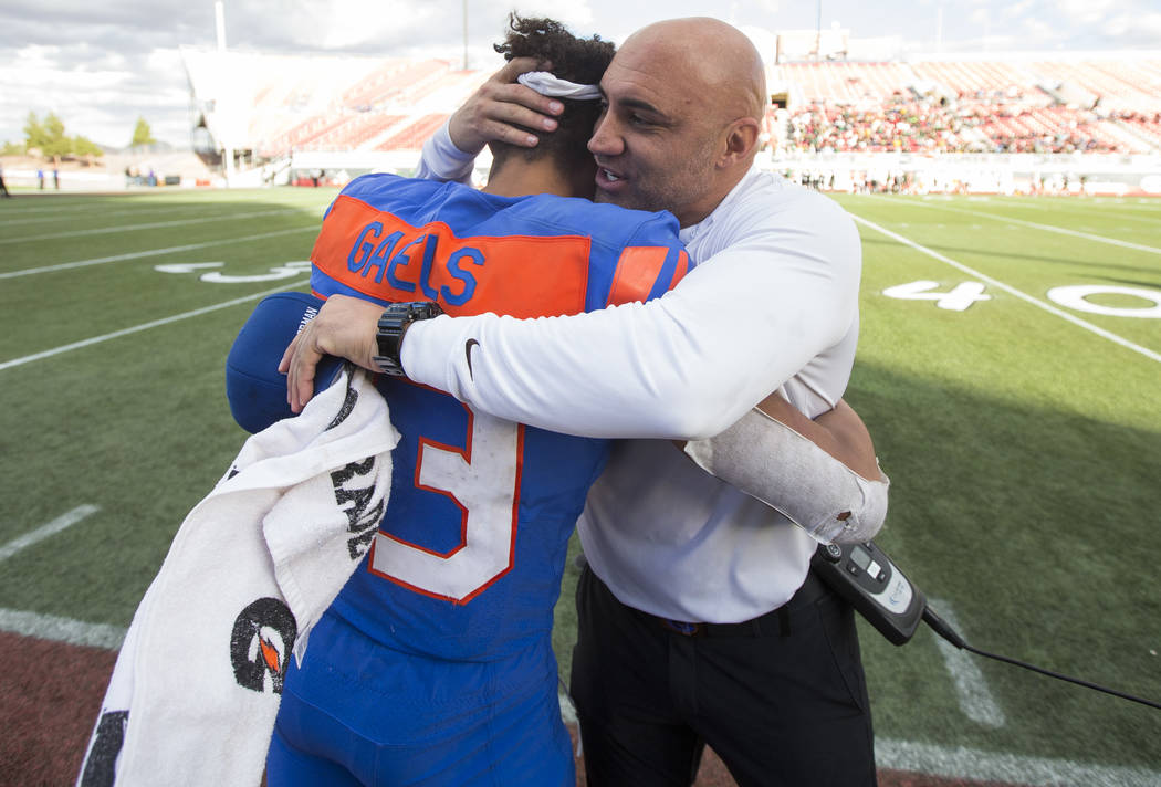 Bishop Gorman coach Kenny Sanchez hugs running back Amod Cianelli (23) after defeating Reno's Bishop Manogue 69-26 in the NIAA high school football championship at Sam Boyd Stadium in Las Vegas on ...