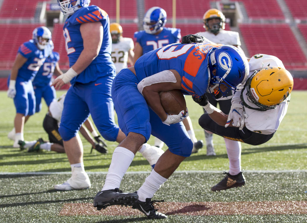 Bishop Gorman running back Amod Cianelli (23) shakes off Reno's Bishop Manogue Mateo Reviglio (3) after scoring a touchdown during the second half of the NIAA high school football championship at ...
