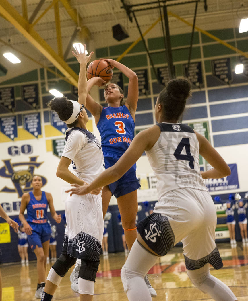 Bishop Gorman's Georgia Ohiaeri (3) shoots over Spring Valley defenders Mackenzie Carcelli, left, and Kiana Turenne (4) during the first half of a varsity basketball game at Spring Valley High Sch ...