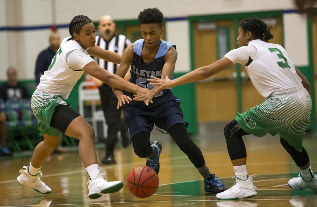 Canyon Springs guard Kayla Johnson (23), center, drives the ball through Green Valley defenders Shelby Clark (5) and Amore Espino (3) during the first half of a varsity basketball game at Green Va ...