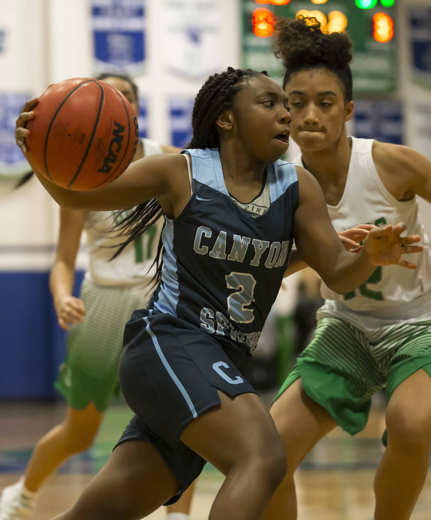 Canyon Springs guard Rajah Thomas (2) dribbles the ball past Green Valley's Rian Anderson (12) during the second half of a varsity basketball game at Green Valley High School in Henderson on Frida ...