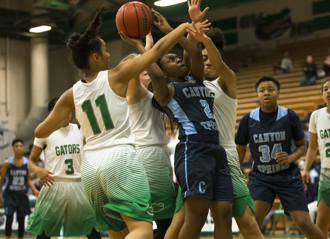 Canyon Springs guard Rajah Thomas (2) takes a shot through Green Valley's Lusi Soifua (11) and Rian Anderson (12) during the second half of a varsity basketball game at Green Valley High School in ...