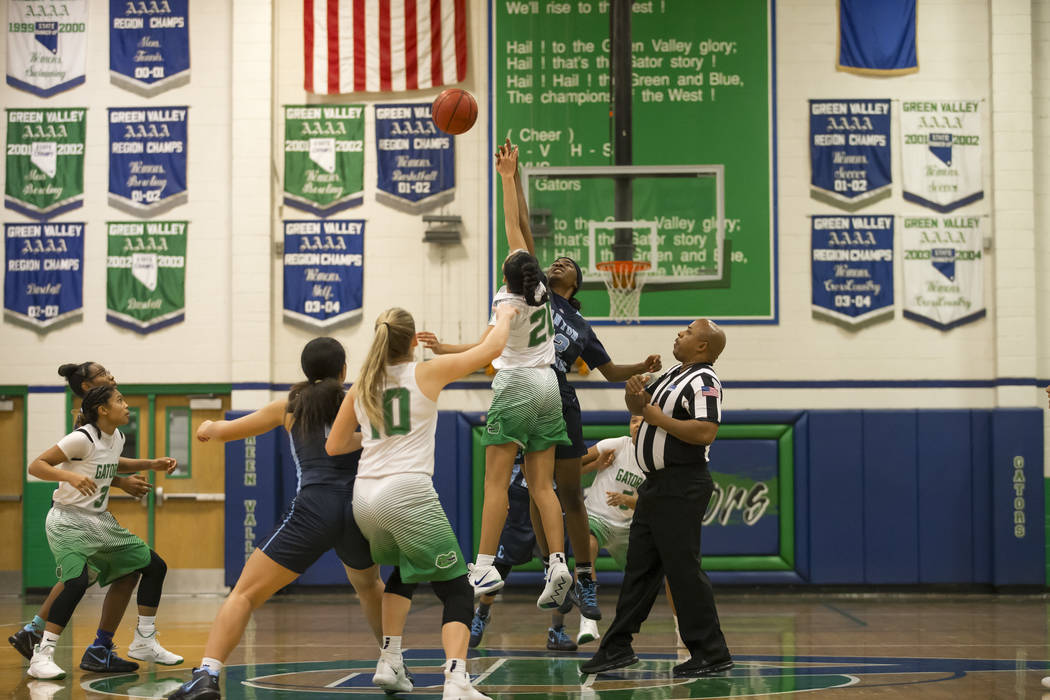 Green Valley's Michelle Lagunas-Monroy (20) and Canyon Springs center Brooklyn Knox (42) tip off to start the first half of a varsity basketball game at Green Valley High School in Henderson on Fr ...