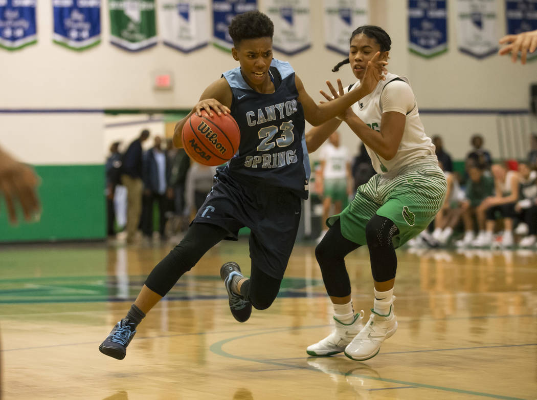 Canyon Springs guard Kayla Johnson (23) drives the ball past Green Valley's Amore Espino (3) during the second half of a varsity basketball game at Green Valley High School in Henderson on Friday, ...