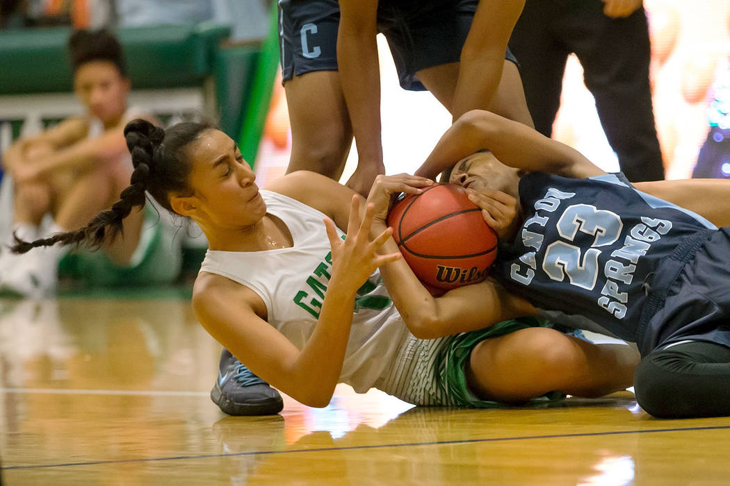 Canyon Springs guard Kayla Johnson (23) and Green Valley's Lusi Soifua (11) fight for the ball during the second half of a varsity basketball game at Green Valley High School in Henderson on Frida ...
