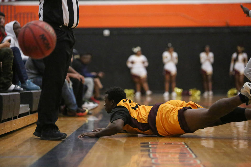 Eldorado's Jalen Malone (24) falls to the ground after attempting to gain possession of the ball during the first half of a basketball game at Chaparral High School in Las Vegas, Monday, Dec. 10, ...