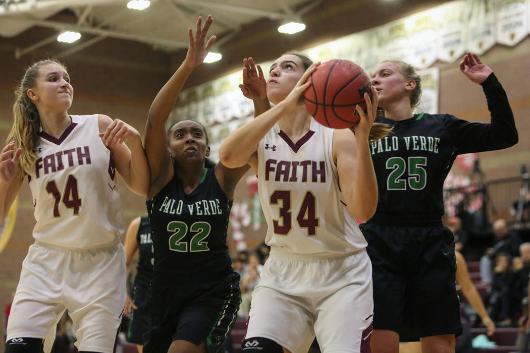 Faith Lutheran's Kelsey Howryla (34) looks to shoot the ball while under pressure from Palo Verde's Kaionna Hanna (22), left, and Palo Verde's Ashley Marushok (25) as Faith Lutheran's Ellie Fried ...
