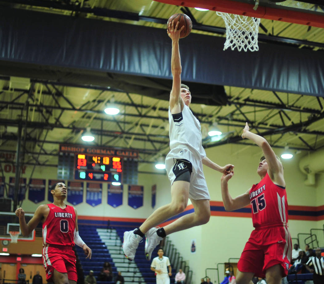 Faith Lutheran's Brevin Walter (23) goes for a lay up over liberty defenders in the fourth quarter of a game between Liberty High School and Faith Lutheran at Bishop Gorman High School in Las Vega ...