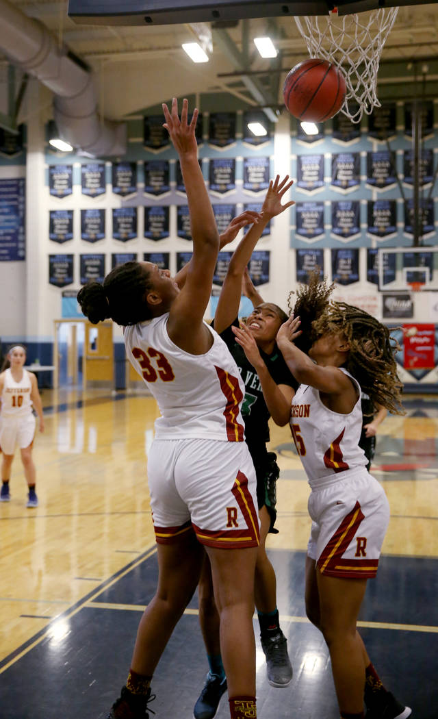 Palo Verde forward Kedrena Johnson, center, goes for a rebound between Thomas Jefferson (Wash.) forwards Nadira Eltayib (33) and Gjianni White (15) in the second quarter of their Las Vegas Holiday ...