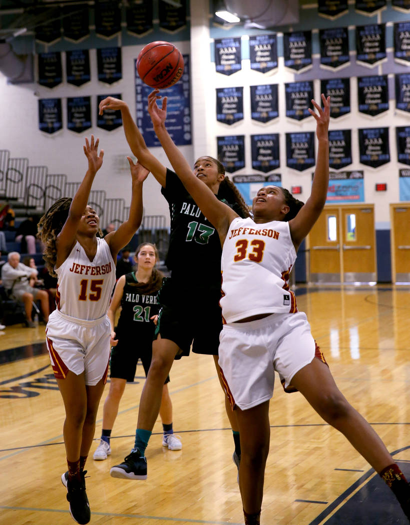 Palo Verde forward Kedrena Johnson (13) goes for a rebound between Thomas Jefferson (Wash.) forwards Gjianni White (15) and Nadira Eltayib (33) in the second quarter of their Las Vegas Holiday Cla ...