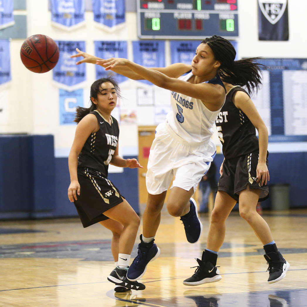Centennial's Jade Thomas (5) throws the ball past West's Rachel Arakawa (15) during a basketball game at Centennial High School in Las Vegas on Saturday, Dec. 29, 2018. Chase Stevens ...