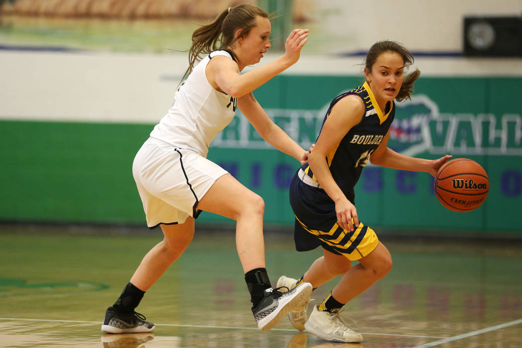 Boulder City's Keely Alexander (14) dribbles the ball up the court as she is pressured by Foothill's Aqui Williams (2) in the girl's basketball game at Green Valley High School in Henderson, Wedne ...