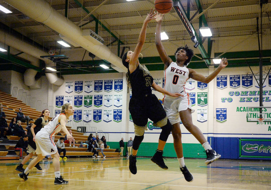 Spring Valley's Garrisen Freeman (32) and West Anchorage's Azaria Robinson (0) jump up for the ball during the second half of a basketball game at Green Valley High School in Henderson, Thursday, ...