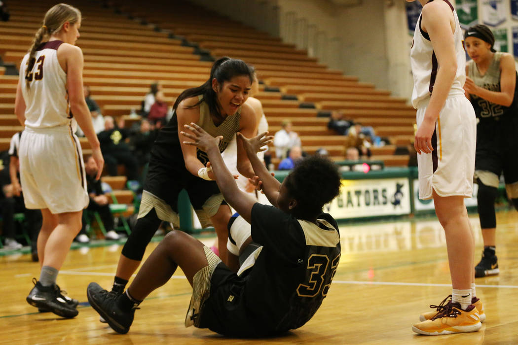 Spring Valley's Chyna Charles (33) gets help getting up from Chelsea Camara (5) after making a shot and receiving an extra shot in the Diamond bracket championship basketball game at Green Valley ...