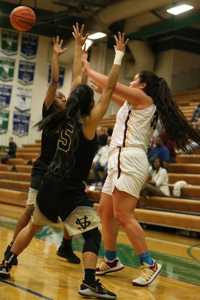 Dimond's Alissa Pili (35) makes a pass under pressure from Spring Valley's Aaliyah Gayles (3) and Chelsea Camara (5) in the Diamond bracket championship basketball game at Green Valley High School ...