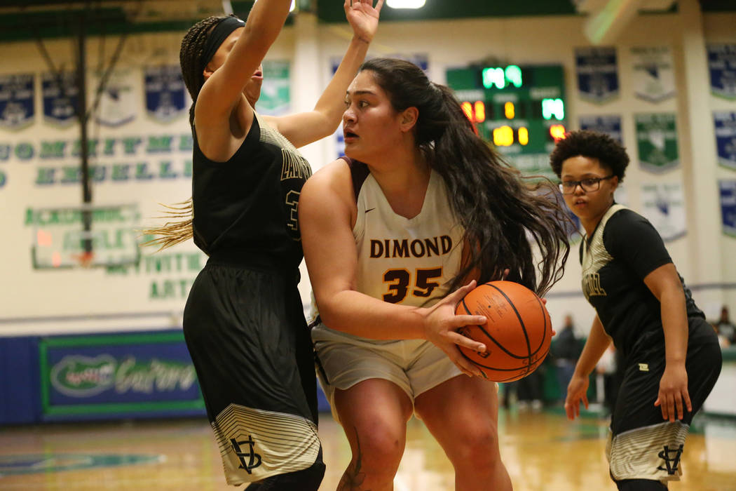 Dimond's Alissa Pili (35) looks for an open pass against pressure from Spring Valley's Garrisen Freeman (32) in the Diamond bracket championship basketball game at Green Valley High School in Hend ...