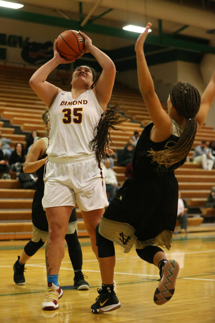 Dimond's Alissa Pili (35) goes up for a shot before getting called for a charge against Spring Valley's Garrisen Freeman (32) in the Diamond bracket championship basketball game at Green Valley Hi ...