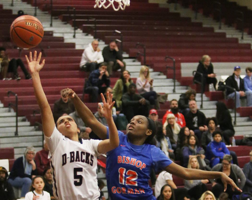 Desert Oasis High School's Eliyjah Pricebrooks (5) attempts a shot past Bishop Gorman High School's Aaliyah Bey (12) at Desert Oasis High School in Las Vegas, Tuesday, Jan. 8, 2019. Bishop Gorman ...