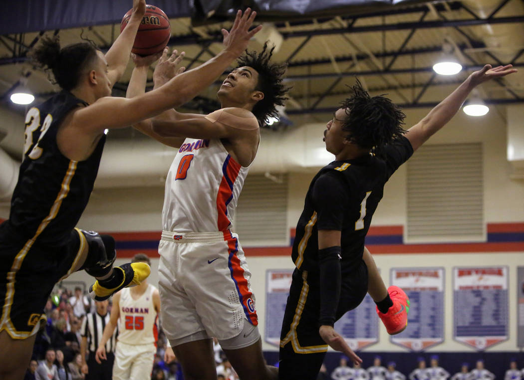 Bishop Gorman's Isaiah Cottrell (0) goes to shoot the ball while under pressure from Clark's Ian Alexander (32), left, and Frankie Collins (1) during the second half of a basketball game at Bishop ...