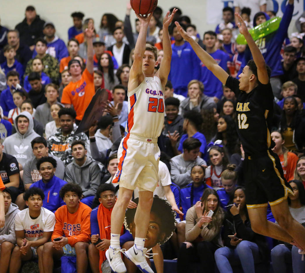 Bishop Gorman's Noah Taitz (20) goes to shoot the ball while under pressure from Clark's Cameron Kimble (12) during the second half of a basketball game at Bishop Gorman High School in Las Vegas, ...