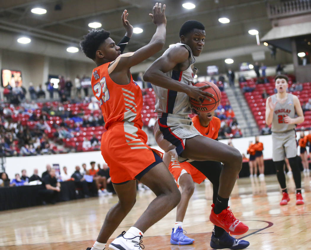 Findlay Prep's Alex Tchikou, right, moves the ball around Bishop Gorman's Mwani Wilkinson (23) during the second half of the annual Big City Showdown basketball game at the South Point in Las Vega ...