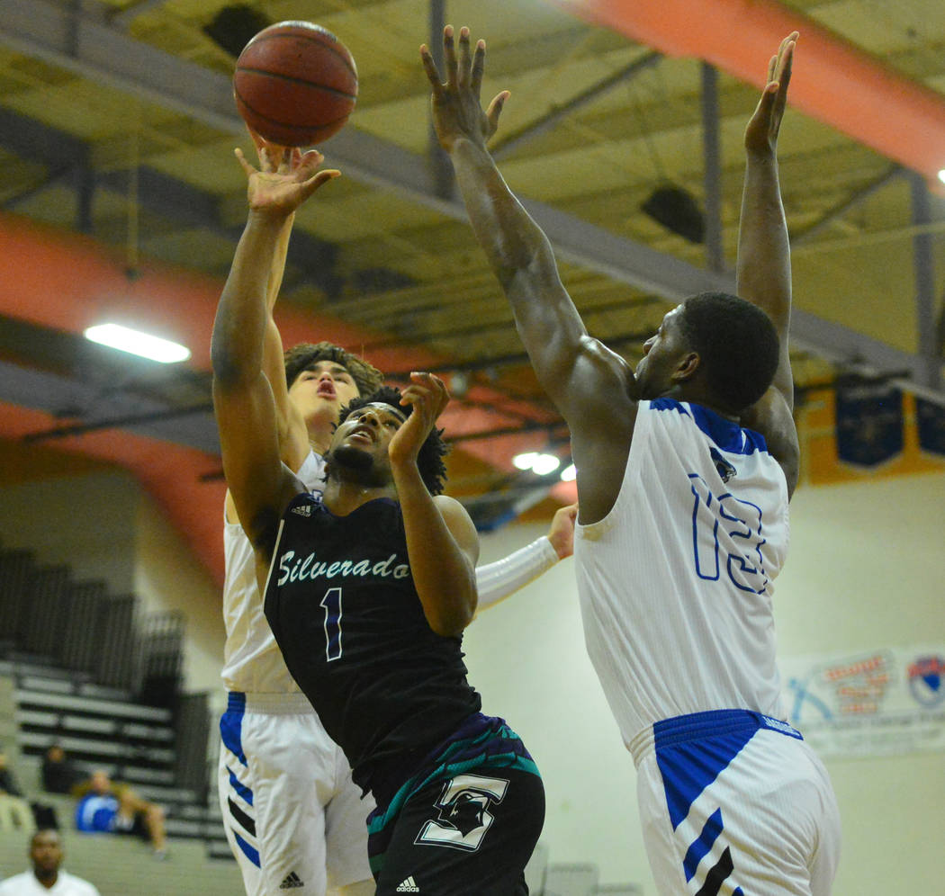 Silverado's Leandrew Menefee (1) tries to sneak a shot through Desert Pines defenders in the fourth quarter of the Desert Pines vs. Silverado High School basketball game at Desert Pines High Schoo ...