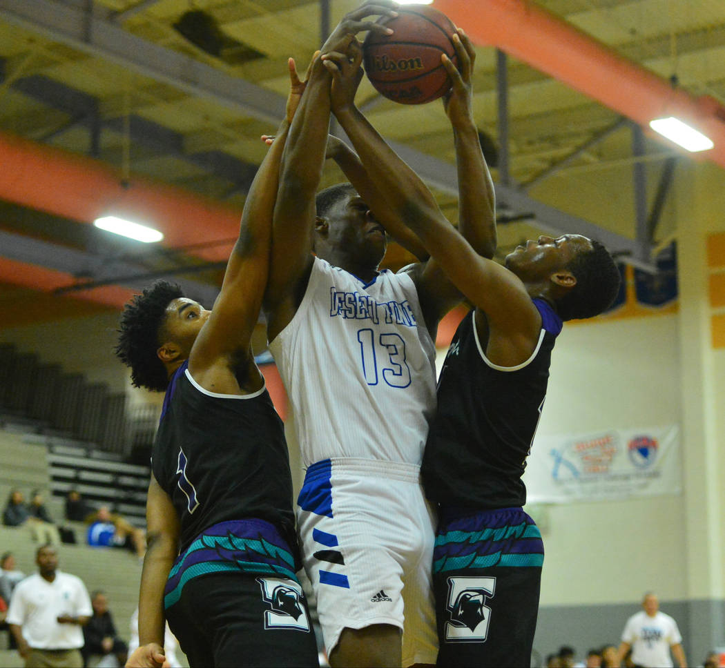 Desert Pines' Darnell Washington (13) catches an elbow to the face while pulling down a rebound in the fourth quarter of the Desert Pines vs. Silverado High School basketball game at Desert Pines ...