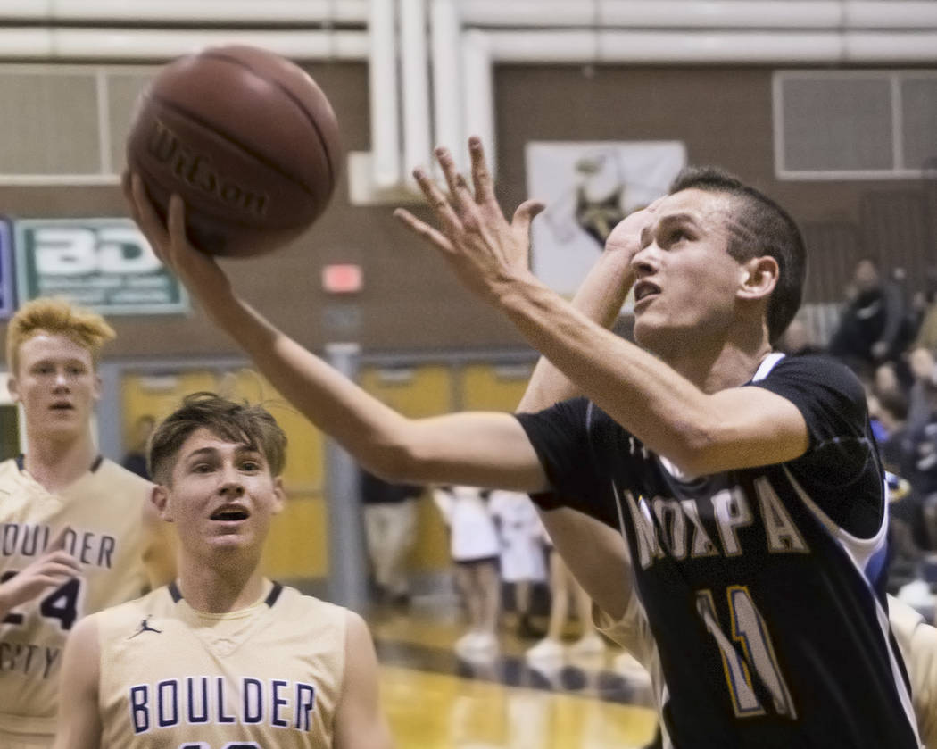 Moapa Valley sophomore guard Lucas Walker (11) drives past Boulder City junior guard Gavin Balistere (10) and sophomore guard Matt Morton (24) in the second quarter on Tuesday, Jan. 29, 2019, at B ...