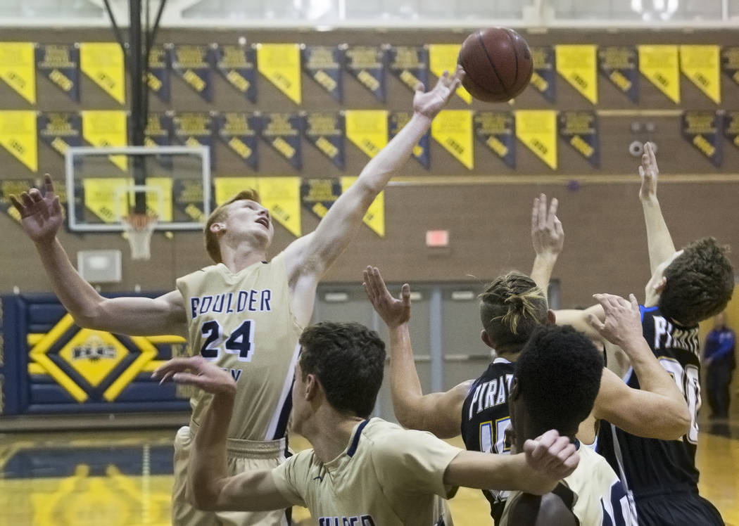 Boulder City sophomore guard Matt Morton (24) fights for a loose ball with Moapa Valley senior forward Jessup Lake (15) and sophomore forward Cameron Reese (25) in the first quarter on Tuesday, Ja ...